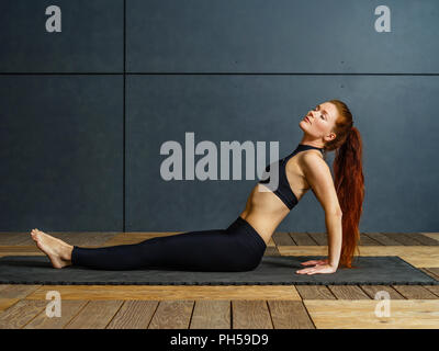 Photo of a beautiful redhead doing yoga on a floor mat in a gym. - Stock Photo