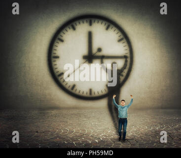 Surreal image of a businessman trying to stop the time. Casting a shadow with hands up holding the clock arrow. - Stock Photo