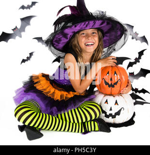 Happy Halloween witch & happy pumpkin. Little girl with a Halloween costume of a witch with hat, striped legs holding two smiley Halloween pumpkins - Stock Photo