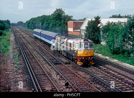 A class 33 diesel locomotive number 33008 'Eastleigh' with a pair of barrier coaches in tow approaching Wimbledon on the 15th July 1992. - Stock Photo