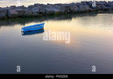 lonely boat at sunset anchored in the small fishing port - Stock Photo