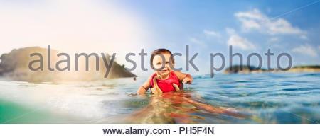 Baby girl in sea - Stock Photo