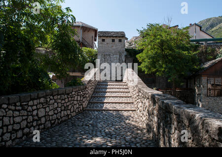 Mostar: Kriva Cuprija (Sloping Bridge), the oldest single arch stone bridge in town built in 1558 as a test before the construction of the Stari Most - Stock Photo