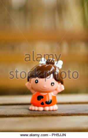 Plastic toy prehistoric woman figure with bone in hair in soft focus - Stock Photo