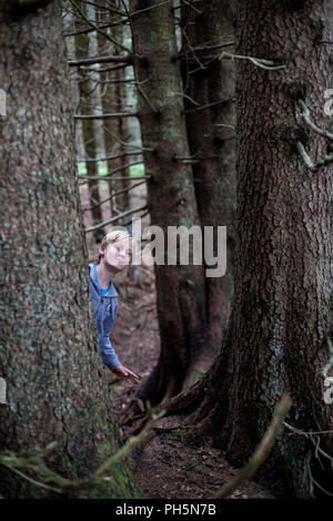 A boy hiding behind the tree in a forest - Stock Photo