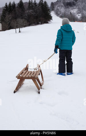 A boy pulling his sleigh up the hill - Stock Photo