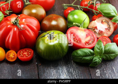 various colorful tomatoes and basil leaves on rustic table. fresh delicious zebra tomato and ccor de boeuf - Stock Photo