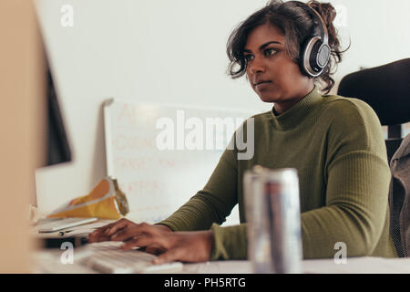 Female programmer working in a software developing company office. Woman wearing headphones coding on desktop computer. - Stock Photo