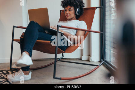 Young african woman sitting relaxed on chair wearing headphones and working on laptop. Female software programmer working at tech startup. - Stock Photo