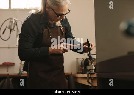 Senior female jeweler shaping and designing the edges of silver ring at her workbench. Mature jewelry designer making ring using tools at her workshop - Stock Photo