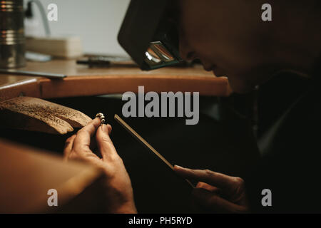 Close up of a female goldsmith working and shaping an unfinished ring with a tool at workbench in workshop. Mature jewelry maker wearing magnifying gl - Stock Photo