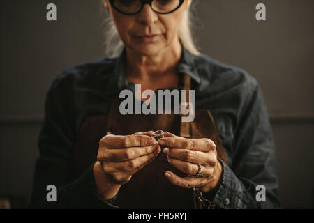 Close up of female jeweler hands examining the silver ring at workshop. Woman goldsmith inspecting jewelry. - Stock Photo