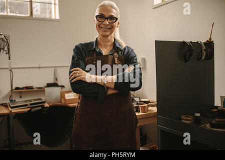 Portrait of confident senior female jeweler standing in her workshop. Woman goldsmith wearing apron and eyeglasses standing with her arms crossed and  - Stock Photo