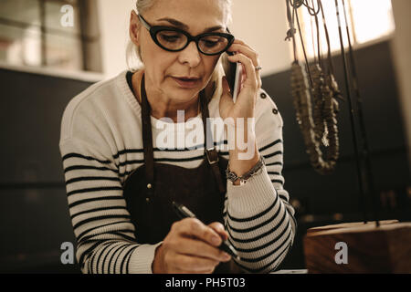 Portrait of senior female jeweler making note and talking on smart phone. Mature woman jewelry designer talking with client over phone and taking note - Stock Photo