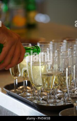 hand holding a bottle of sparkling wine, pouring in champagne cups - Stock Photo