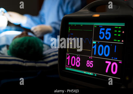 Electrocardiogram in hospital surgery operating emergency room showing patient heart rate with blur team of surgeons in background. Health and medicin - Stock Photo