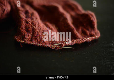 knitting brown wool cardigan, work in progress, on a black background - Stock Photo