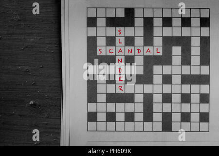 Scandal and slander written in red as solutions to a newspaper crossword puzzle on wood - Stock Photo