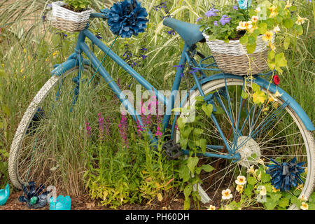 RHS Hampton Court Flower Show 2018, London, UK. Blue classic ladies bicycle with planted baskets in an creative and inspiring  cottage style garden. - Stock Photo