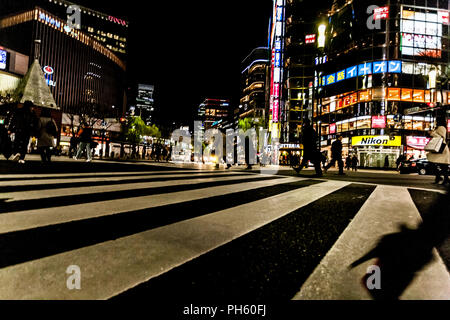 Tokyo, Japan - January 14, 2010: Pedestrians crossing the street at the heart of Ginza District in Tokyo. Ginza crossing at night. Blurred motion. - Stock Photo
