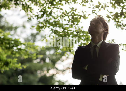 Young businessman in a suit standing with his arms crossed in a green forest looking upwards in a meditative pose and expression. - Stock Photo