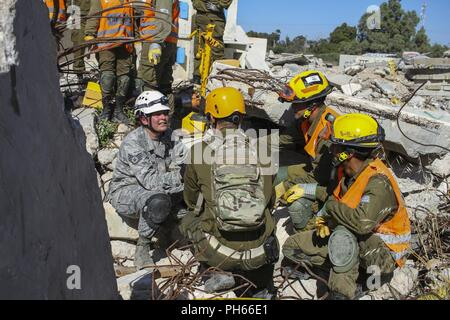 TEL AVIV, Israel – Air Force Staff Sgt. Abigail Adams, a search and extraction medic with the 19th CBRN Enhanced Response Force Package, discusses with Israeli Defense Force search and extraction soldiers how best to remove the simulated victim from the rubble during the final exercise of United Front VII at Zikim Training Base June 20, 2018. Due to the risk of crushing injuries, rescuers have to be cautious when removing debris from victims to prevent causing further injury. - Stock Photo