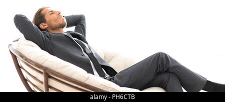 young businessman sitting in large comfortable armchair. - Stock Photo