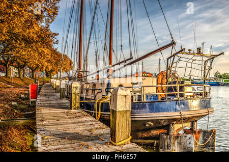 Enkhuizen, The Netherlands, October 26, 2015: historic sailing vessel moored at the wooden boardwalk at the Buitenhaven (Outer Harbour) - Stock Photo