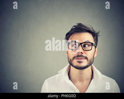 Handsome bearded man looking up in contemplation making decision on gray background - Stock Photo
