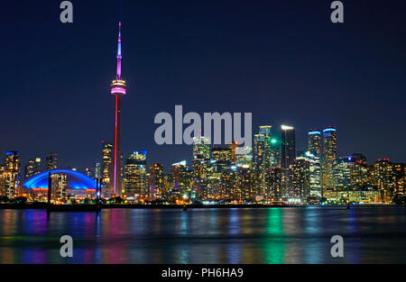 Toronto evening skyline including downtown landmark buildings CN Tower, Roger's Centre and office skyscrapers in financial district and waterfront - Stock Photo