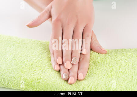 Beautiful woman hands with orange manicure on finger nails on green towel in beauty studio. Close up, selective focus - Stock Photo