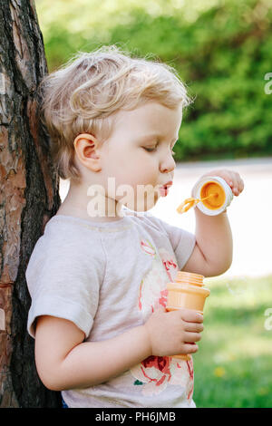 Portrait of cute funny little blond Caucasian child girl toddler standing in the green forest field meadow blowing soap bubbles, bright summer day, su - Stock Photo