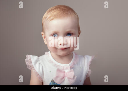 Closeup portrait of cute adorable white blonde Caucasian baby with blue eyes girl looking in camera. Child girl smiling posing in studio on plain ligh - Stock Photo