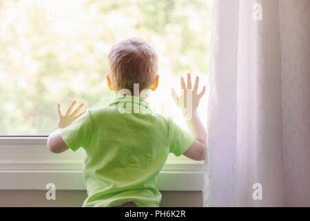 Portrait of white Caucasian child boy at home looking out of window outside. View from back. Kid waiting for someone - Stock Photo