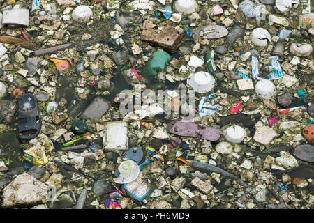 Plastic bags, bottles, polystyrene and other trash contaminates the water of a lagoon in Pushkar, India - Stock Photo