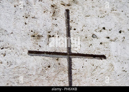 An engraved cross painted in black on a tombstone. Shot in Italy in 2018. - Stock Photo