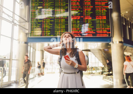 Theme travel and tranosport. Beautiful young caucasian woman in dress and backpack standing inside train station or terminal looking at a schedule holding a red phone, uses communication technology - Stock Photo