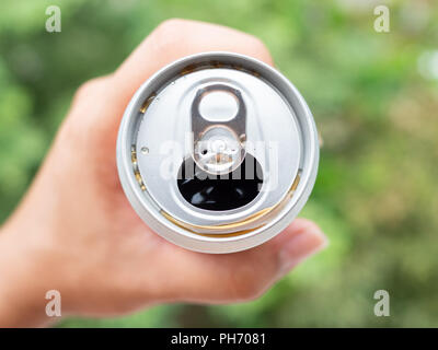 Opened can with sparkling water in hand on green nature background. - Stock Photo