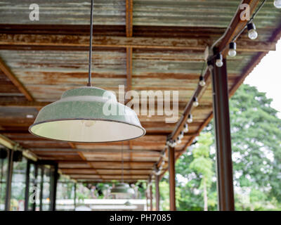 Vintage old ceiling lamp and light bulbs on retro cafe and tree background. - Stock Photo
