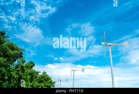 Horizontal axis wind turbine with blue sky and white clouds near green tree. Wind energy in eco wind farm. Green energy concept. Renewal energy. Alter - Stock Photo