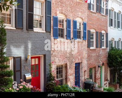 Neighborhood of brick row houses on a quiet street - Stock Photo