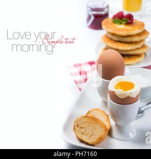 Fresh breakfast with eggs, pancakes, jam and juice on white background. Завтрак с двумя яйцами в мешочек, сырниками, малиновым вареньем и апельсиновым - Stock Photo