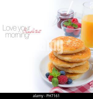 Fresh breakfast with cottage cheese pancakes, fresh berries, jam and juice on white background. Завтрак с сырниками, свежими ягодами, малиновым варень - Stock Photo
