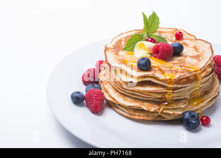 Pile of pancakes with berries and honey on white plate Оладьи с ягодами и медом на белой тарелке - Stock Photo