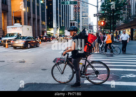New York City, USA - June 21, 2018: Hispanic courier on bicycle in crosswalk in New York City at dusk - Stock Photo