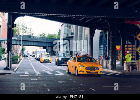 New York City, USA - June 22, 2018: Yellow taxi cab traveling under High Line bridge in Manhattan - Stock Photo