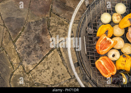 Assortment of grilled vegetables on metal grate of round big outdoor grill standing on natural stone pavement. Healthy eating concept. Selective focus - Stock Photo