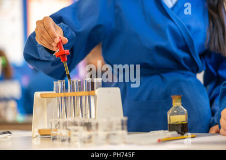 Coloured test tubes photographed in a school classroom during a science lesson and experiment. - Stock Photo