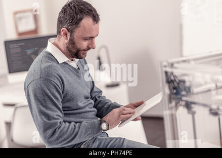 Handsome adult man sitting at the office - Stock Photo