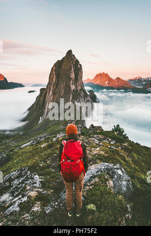 Adventurous woman enjoying sunset Segla mountain hiking solo traveling outdoor in Norway active vacations backpacking healthy lifestyle - Stock Photo